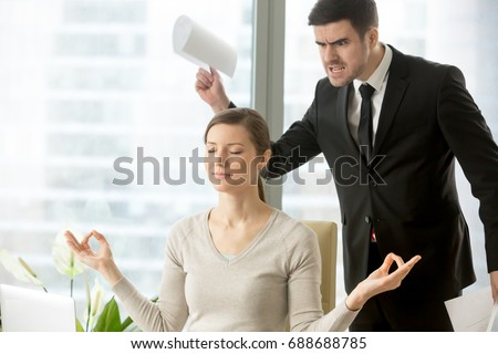 Calm attractive businesswoman practicing yoga at work, meditating in office with eyes closed, ignoring angry bad boss standing behind her back, avoiding negative people, positive thinking, no stress