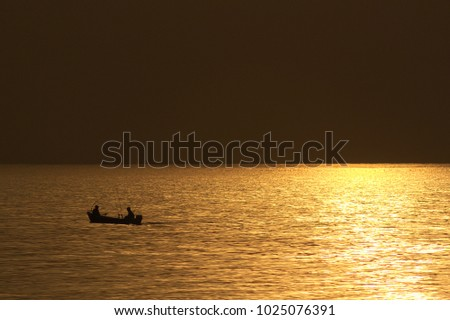 Calm Baltic sea during sunset with orange/copper tint and specular highlights from (not framed) sun filtered through thin clouds on the right, with  Silhouette of the distant angler boat on the left