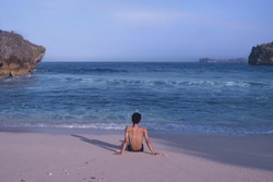 calm beach atmosphere with a man staring at the sea