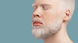 Calm bearded albino man with closed eyes resting against turquoise background. Extraordinary guy with white hair, eyelashes and brows. Panorama with empty space. Albinism, uncommon appearance concept