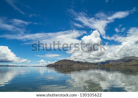 Calm beautiful rural landscape with a lake (Titicaca) and sky reflected