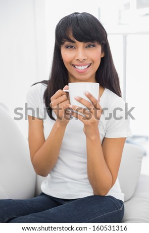 Calm beautiful woman holding a cup smiling at camera sitting in bright living room
