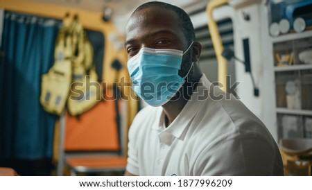 Calm Black African American EMS Professional Paramedic Looks at Camera While Wearing a Safety Face Mask in Ambulance Vehicle. Successful Emergency Medical Technician Outside the Healthcare Hospital. ストックフォト ©