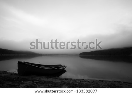 calm black and white landscape with lake and lonely boat