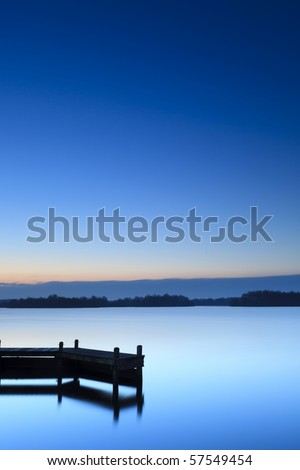 Calm blue sunset at a lake with jetty