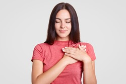Calm brunette female with closed eyes, keeps both palms on heart, feels gratitude, being touched by something, dressed in casual pink t shirt, isolated over white background. Body language concept