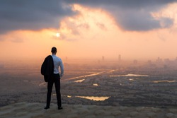 Calm business man standing above on rooftop looking at the city view at sunset.