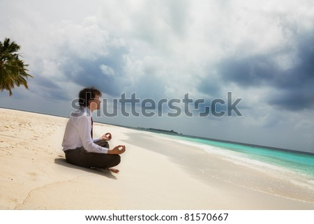 Calm businessman sitting on the shore on the white sand