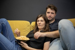 calm, concentrated, unemotional guy and girl hugging lying on couch with popcorn in their hands and watching TV, YouTube channel, online broadcast. Unhealthy habits lead to weight gain copy space