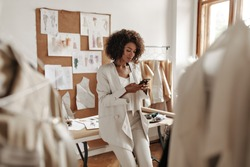 Calm curly brunette dark-skinned woman in white suit leans on desk in office of fashion designer and holds phone.
