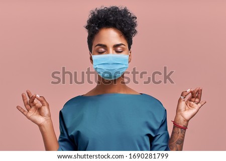 Calm doctor relaxing meditation wearing respiratory mask, no stress free relief at work concept, mindful peaceful young female paramedic practicing breathing yoga exercises on beige wall. Coronavirus