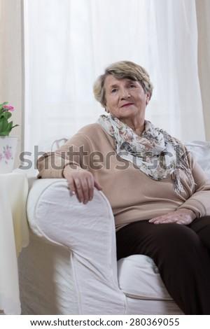 Calm elderly lady sitting alone in her room