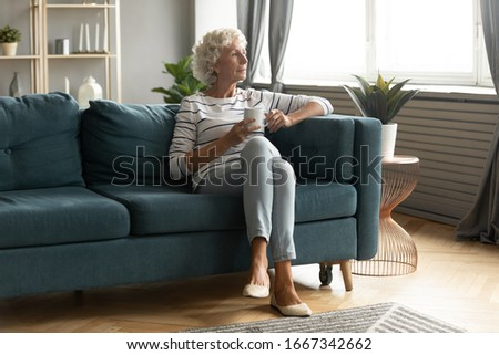 Calm elderly woman sit on comfortable couch in living room drink tea look in window distance thinking or dreaming, pensive thoughtful mature 50s grandmother enjoy coffee relax on sofa at home