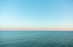 Calm evening sea surface with clear blue sky. Evening seascape.