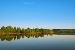 calm expanse of pond water on a bright sunny day with trees with green leaves on the opposite bank.
