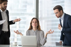 Calm female worker meditate at workplace managing stress not paying attention to angry colleagues, businesswoman sitting in lotus pose practicing yoga staying calm not involved in conflicts or dispute