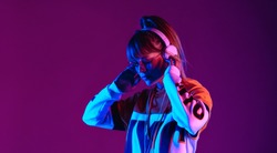 Calm girl wear stylish glasses headphones listen music at purple background.