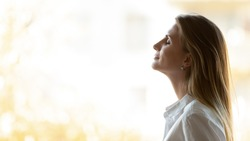 Calm happy business woman breathing fresh air standing at window, mindful lady take deep breath meditate feel no stress free relief enjoy wellbeing practice yoga exercise at home office, side view
