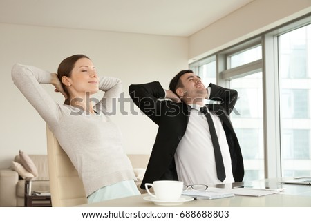 Calm happy businessman and businesswoman relaxing with eyes closed, hands behind head sitting in ergonomic office chairs, smiling executives enjoying break, lounge after work in modern office