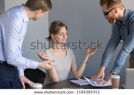 Calm happy businesswoman meditating in office ignoring not listening to colleagues, funny female boss practicing yoga at stressful job keeping mental emotional balance, no stress at work concept