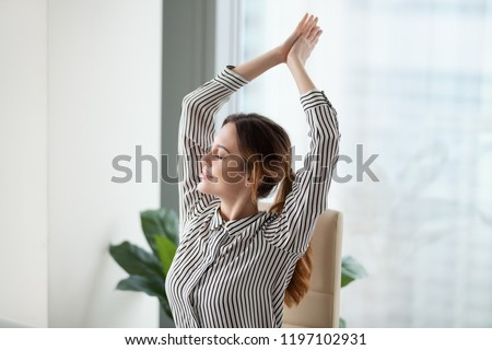 Calm happy businesswoman relaxes in workplace during a break. Smiling woman stretching on work chair, enjoys at work. Relaxation after work is finished. Break, pause.