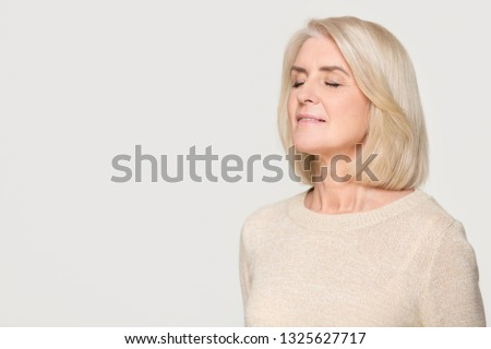 Calm happy mature mid aged woman inhaling taking deep breath of fresh air feel no stress, mindful old lady meditating relaxing advertise freshener isolated on white grey studio background, copy space