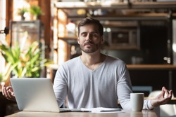 Calm healthy businessman meditate at work desk feeling zen no stress free relief, mindful young man taking break doing yoga exercise relax breath fresh air for peace of mind sit in office cafe