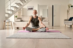 Calm healthy serene old middle aged senior tattooed man meditating with eyes closed sitting in yoga pose in living room at home. Breathing exercises, meditation, no stress, peace of mind, zen concept.