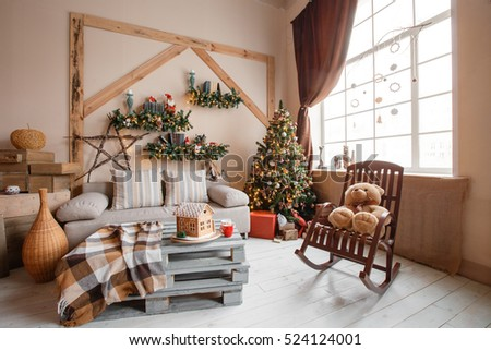 Calm image of interior modern home living room decorated christmas tree and gifts, sofa, table covered with blanket.