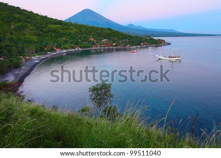 Calm lagoon with sail boat and buildings in forest on a hill side