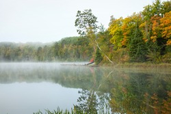 Calm lake and colorful trees in northern Minnesota on a misty autumn morning