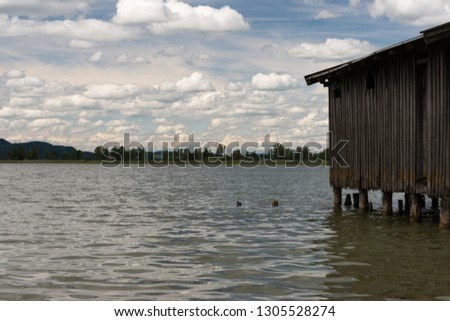 calm lake Kochel in Bavaria with boathouse and a cloudy sky #1305528274