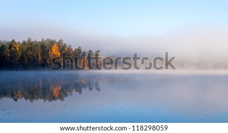 Calm lake panoramic landscape with fog in cold autumn morning