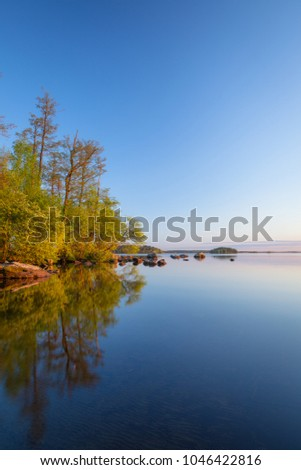Calm lakeside at sunset and rocks on the water #1046422816