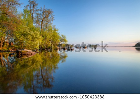 Calm lakeside at sunset and rocks on the water #1050423386