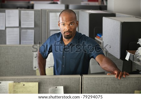 Calm Latino office worker standing in his cubicle