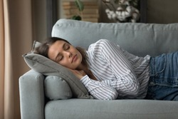 Calm millennial Caucasian woman lying relaxing on couch in living room sleeping taking nap. Tired exhausted young female rest on sofa at home daydream relieving negative emotions. Stress free concept.