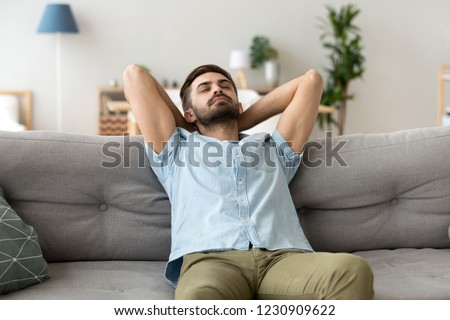Calm millennial man relax on cozy couch hands over head sleeping or taking nap, peaceful male lying on sofa with eyes closed having rest or visualizing, tired guy fall asleep chilling at home