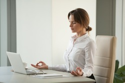 Calm mindful businesswoman meditating at office desk with eyes closed, female executive practicing yoga at workplace enjoying mental emotional mind balance reducing no work stress free relief concept