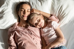Calm mother with little 6s 7s daughter sleeping together lying down on pillow in comfortable bed, caring mom and lovely kid, top above view. Healthy nap at daytime, repose, relaxation moment concept