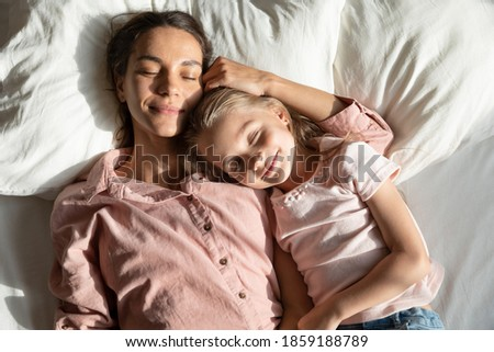 Calm mother with little 6s 7s daughter sleeping together lying down on pillow in comfortable bed, caring mom and lovely kid, top above view. Healthy nap at daytime, repose, relaxation moment concept Photo stock ©