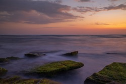 Calm ocean long exposure. Stones covered by green moss in mysterious mist of the sea waves. Concept of nature background. Sunset scenery background. Soft focus. Mengening beach, Bali, Indonesia.