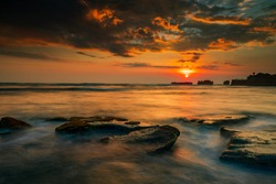 Calm ocean long exposure. Stones in mysterious mist of the sea waves. Concept of nature background. Sunset scenery background. Sun on horizon. Soft focus. Cloudy sky. Mengening beach, Bali, Indonesia