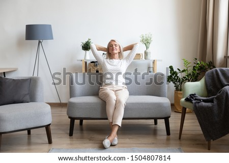 Calm older woman relaxing on comfortable sofa at home, happy mature female with hands behind head enjoying weekend, stretching on couch, resting and daydreaming, leaning back, no stress concept