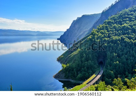 Calm on Lake Baikal. Large-scale top view of Lake Baikal and the section of the Circum-Baikal Railway at the Irkutsk portal of tunnel No. 33. In the background the mountains of Khamar-Daban