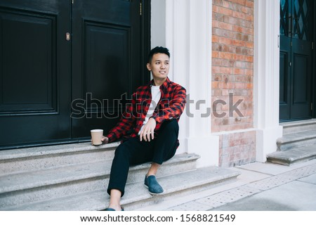 Calm pensive adult Asian male in casual clothes looking away and thinking while sitting on stairs and holding takeaway cup of beverage against back door at entrance of building