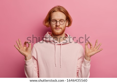 Calm relaxed ginger adult man holds hands in mudra gesture, meditates indoor, closes eyes and does yoga, feels peaceful, has eyewear and sweatshirt, has good patience. Zen and lifestyle concept