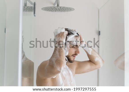 Calm relaxed handsome young man with muscular torso and foamy head taking shower, washing hair with antidandruff shampoo, standing under showerhead with pouring water, caring for routine hygiene. Stock photo ©