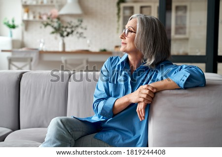 Photo of  Calm relaxed mature older woman relaxing sitting on couch at home. Peaceful middle aged grey-haired lady resting on sofa in modern living room enjoying lounge and no stress, looking away, thinking.