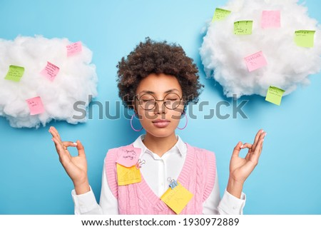 Calm relaxing female office worker feels relieved and stress free meditates indoor keeps eyes closed surrounded with colorful sticky notes takes break from work for mental balance avoids stressful job Stock photo ©